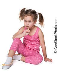 Upset little girl sits on the floor
