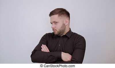 Young Bearded Dark Haired Man In Black Stylish Shirt On White Background, Upset Male Hands Crossed And Makes A Grimace On His Face. The Concept Of People Who Are Offended