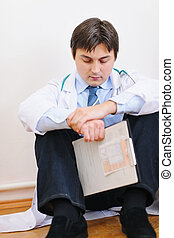Upset male medical doctor sitting on floor