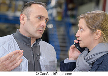 upset male worker talking to female colleague in warehouse