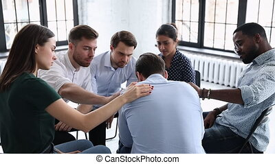 Upset man get psychological support from diverse friends counselor helping at group therapy, male patient feel pain depression share problem addiction during counseling meeting rehab session concept