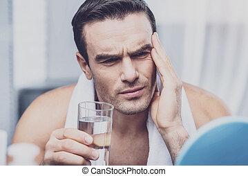 Upset man having sharp headache