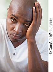 Upset man sitting on the couch looking at camera