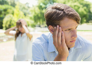 Upset man thinking after a fight with his girlfriend in the park on a sunny day