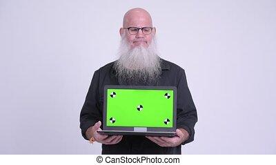 Upset mature bald bearded man thinking while showing laptop