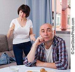 Upset mature man sitting while quarrel with wife at home ...