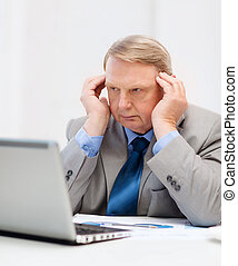 upset older businessman with laptop in office