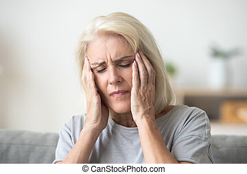 Upset older woman touching temples aching head feeling strong he