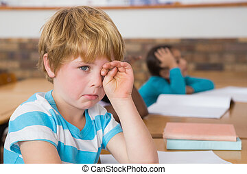 Upset pupil sitting at his desk at the elementary school