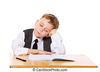 homework - Upset schoolboy doing homework isolated on white
