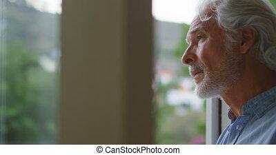 Upset senior man looking through window 4k - Upset senior...