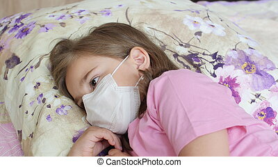 Upset sick child girl lying on a bed
