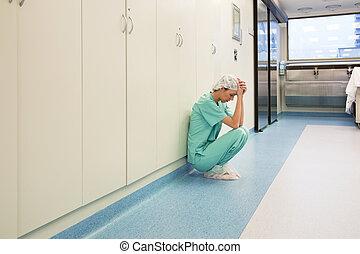 Upset surgeon sitting alone