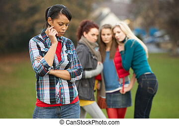 Upset Teenage Girl With Friends Gossiping In Background