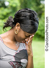 Upset Woman - A young woman holds her hand on her forehead ...