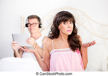Upset Woman and Man in Bed with Computer Tablet