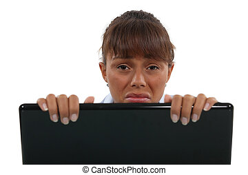 Upset woman behind laptop