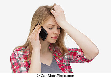Upset woman holding a mobile phone against a white...