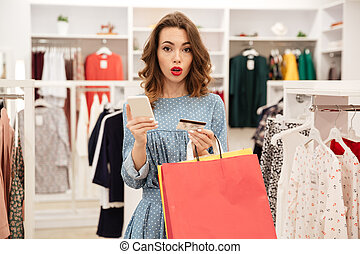 Upset woman holding credit card and packages