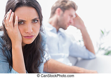 Upset woman holding her head next to her partner