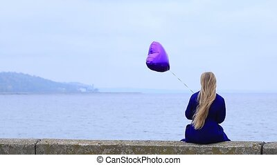 Upset woman holding violet balloon - Back view of lonely ...