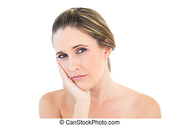Upset woman looking at camera with a toothache