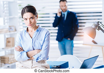 Upset woman pouting her lips while sitting with her arms crossed
