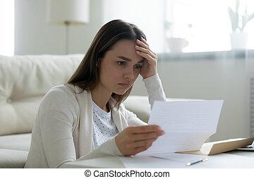 Upset woman read unpleasant news in letter
