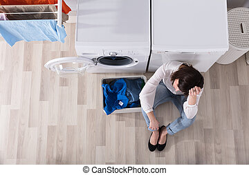 Upset Woman Sitting At Laundry Room