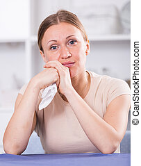 Upset woman sitting at table - Portrait of upset woman ...
