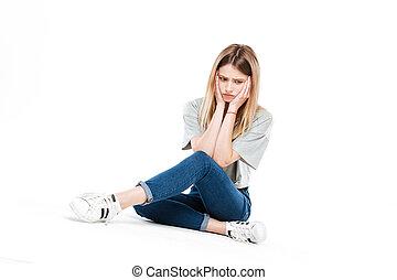 Upset woman sitting cross-legged - Pensive upset blonde...