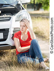 Upset woman sitting on ground and leaning on broken car