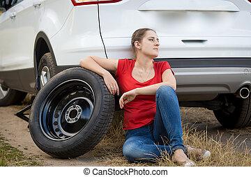 Upset woman sitting on ground at broken car