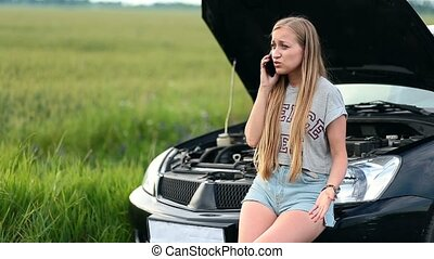 Upset woman talking on phone near broken car - Upset...