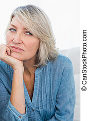 Upset woman thinking at home on couch