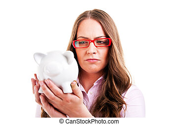 Upset woman wearing glasses holding piggy bank. Expensive eyewear glasses concept. Young female business woman isolated on white background.