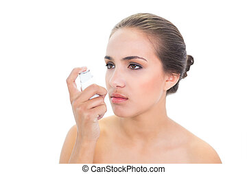 Upset young brunette woman holding an inhaler