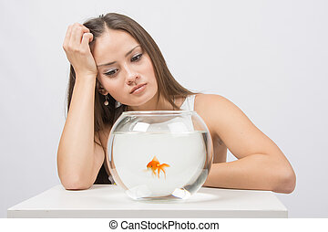 Upset young girl looking at goldfish in a fishbowl