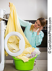 Upset young woman cannot remove stains off bed linen - ...