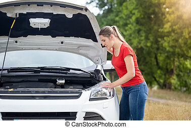 Upset young woman looking on overheated engine of her broken car