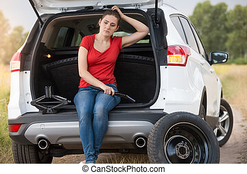 Upset young woman sitting in open car trunk on deserted road at countryside and waiting for help