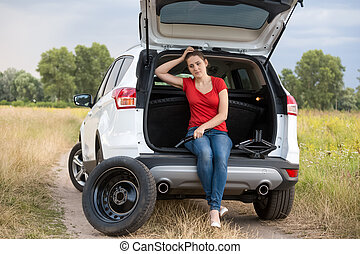 Upset young woman sitting in open trunk of broken car at field