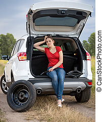 Upset young woman sitting in open trunk of broken car in field