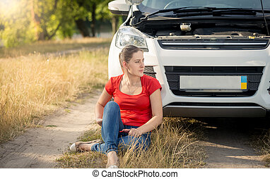 Upset young woman sitting on ground and leaning on her broken car on countryside road