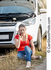 Upset young woman sitting on ground next to broken car calling car service for help