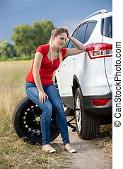 Upset young woman sitting on spare wheel of broken car in field
