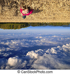 Attractive young teenage white Caucasian female floating above a beautiful field landscape with upside down clouds