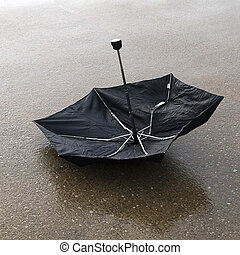 Upside down broken umbrella on wet parking lot - Black ...