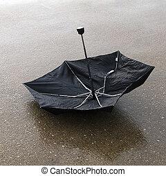 Upside down broken umbrella on wet parking lot - Black...