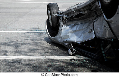 A silver car upside-down on a city street after a car accident